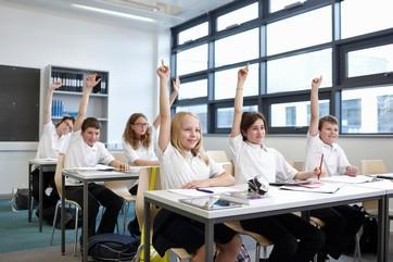 Group of schoolchildren with hands raised in classroom